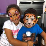girl with butterfly face paint and boy with tiger face paint
